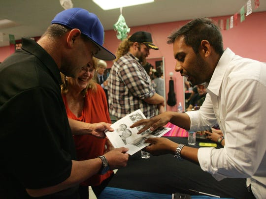 "Juan Canchola-Ventura, right, co-author of the ""Mexican-American Baseball in Ventura County"" book, points out photos in the book to Oxnard College softball coach Wally Barnett Sept. 23 during a book signing  event at the Cafe On A in Oxnard."