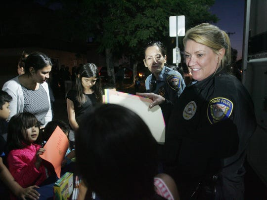 Oxnard Police Department Traffic Service assistants Michele Turner (right) and Edith Villalobos supervise a table Monday for children to write letters and make crafts for the children who were injured in last week's crash.