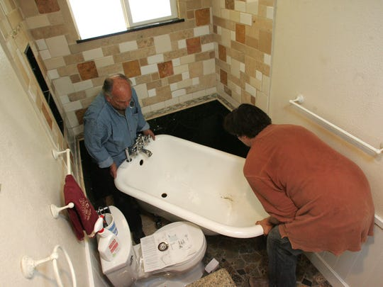 Plumber Phil Hall (left) and Derek Franz install a tub that will be connected to a graywater system in the Browne residence in Camarillo.