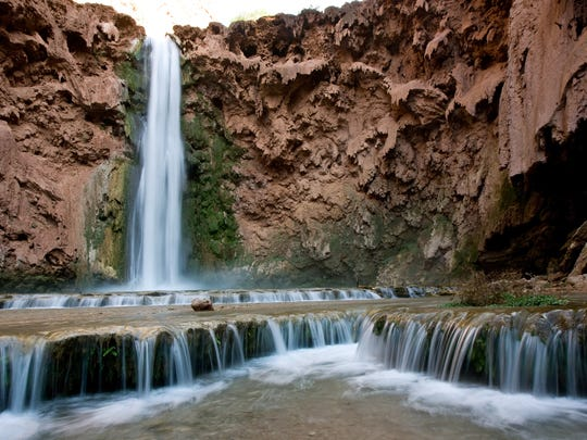 Water flows from Mooney Falls, one of the waterfalls that draws tourists from the U.S. and elsewhere into Havasu Canyon.