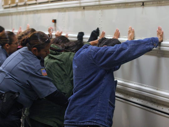 Varios inmigrantes son registrados por agentes del ICE, durante su detención.