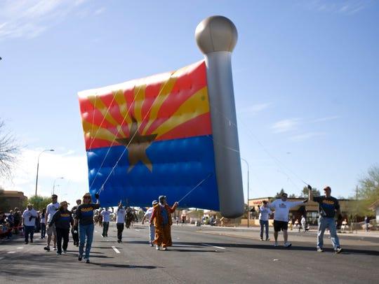 A huge Arizona flag balloon floats down Scottsdale
