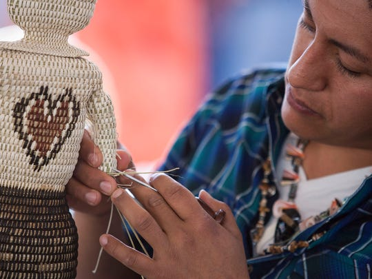 """Jess Eduardo Moreno works on a woven figurine representing the """"man in the maze"""" at the 57th annual Indian Fair and Market at the Heard Museum in Phoenix Saturday March 7, 2014."""
