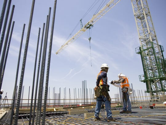 Iron workers work on top of the Sheraton hotel in downtown