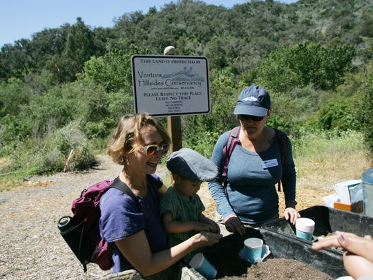 """Sonia Kroth (left) and her son Mateo Kroth, 2, receive instructions on how to make milkweed """"seed balls"""" from Adrienne Stephens, of Ventura Hillsides Conservancy, during the second annual """"Monarch Madness"""" milkweed planting event, hosted by the Ventura Hillsides Conservancy, at the Big Rock Nature Preserve in Ventura. The organization is now called the Ventura Land Trust."""