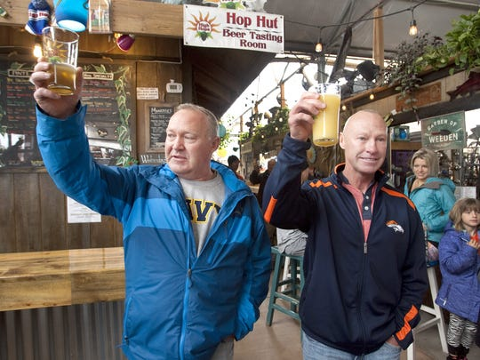 Brothers David, left, and Mark Jacoby toast their late brother, Johnny, who was fatally shot while riding his bicycle May 18, 2015. The brothers were at High Hops Brewery during the conclusion of the second annual Johnny's Community Run at Windsor Lake-Boardwalk Park on April 29.
