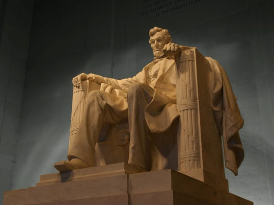 Marble statue of Abraham Lincoln sitting again gray concrete