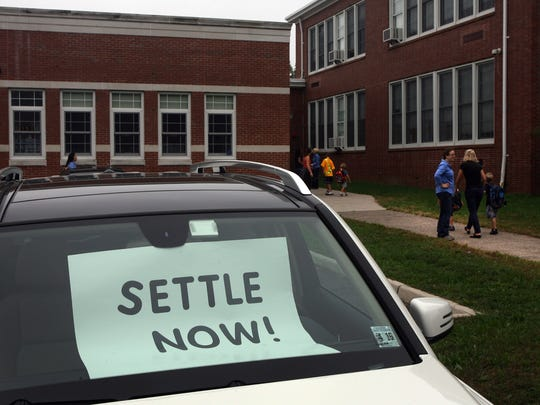 Parents drop kids off at Oradell Elementary School on Sept. 23, 2011. Oradell teachers and staff demonstrated in front of the school before classes started. Cars in the school parking lot displayed signs calling for negotiation and settlement.