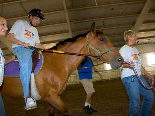 "New Castle County's Carousel Park and Riding Center shows off their TRAC  (Therapeutic Riding At Carousel) program Horses for Heros to help vets deal with disabilities by riding horses. Pictured: Ed Walker concentrates on his riding ""Wire"" with the help of Katie Kokoszka (left) and Cindy Deyo on June 25, 2008."