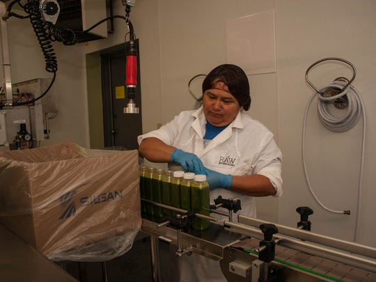 Raw Generation worker Jacqueline Olivera, seals the caps of the juices in Long Branch. She lets the juices settle before packing and shipping.
