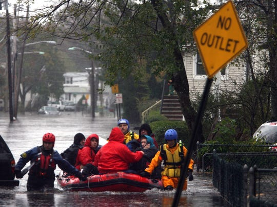 Rescue workers use a boat to evacuate residents on Eckel Road in Little Ferry, bringing them to dry land, Oct. 30, 2012.