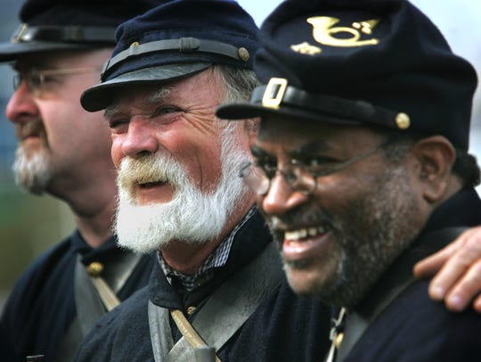 Civil War re-enactor Harry Dolph, center, shares a