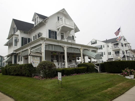 The Beacon House is   lovely Victorian, circa 1879, with wrap-around porches with green-and-white awnings.