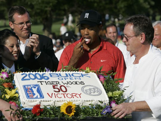 Tiger Woods samples his cake in front of the crowd at the 2006 Buick Open following his 50th PGA Tour victory.