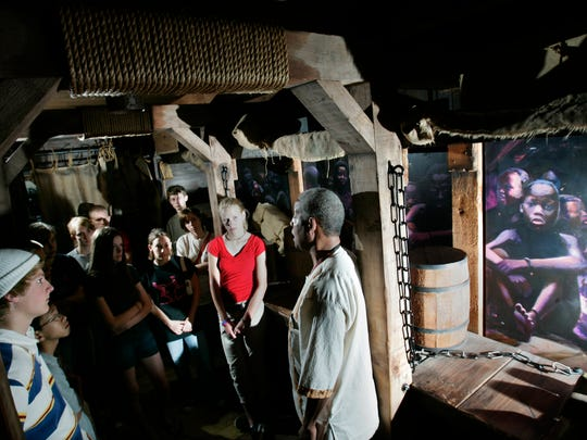 Tony Courtney (right) leads members of City on a Hill Milwaukee, a Christian not-for-profit organization, through the replica of a slave ship at  America's Black Holocaust Museum in 2005.