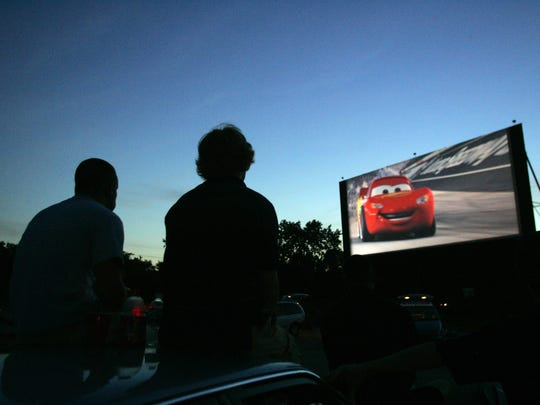 Movie goers sit atop their vehicle as they watch the