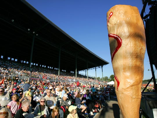 A giant corn dog stands in front of a packed grandstand