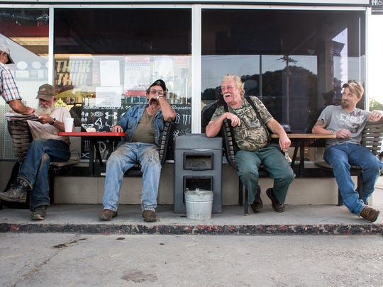 "Tom Orr, left, Joe Waldroup, Roy Grooms and Robert Jordan sit outside Time-Out gas station in Robbinsville Wednesday night, Aug. 27, 2014. Waldroup and Grooms are both former moonshine makers, and Grooms appears on the Discovery Channel show ""Moonshiners"". They both continue to work construction jobs here and there, they said. ""The smartest people that come from Graham County are the ones who graduated and got out of here,"" Waldroup said of the county with limited jobs. Robbinsville's main industry, Stanley Furniture, closed in July, putting more than 400 people from the region out of work."