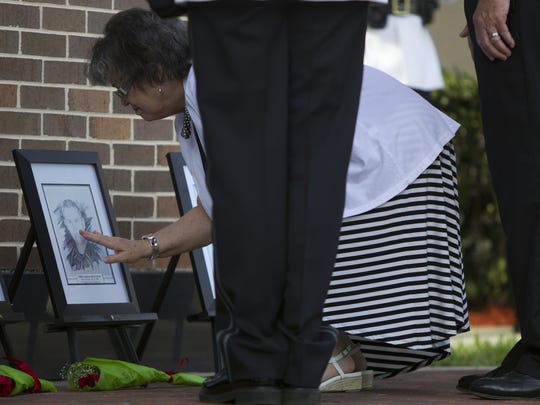 Bonnie Rickards, mother-in-law of fallen Fort Myers Police Officer Andrew Widman, touches his photo after placing a single rose on the ground at the Fallen Officers Memorial Service, held Monday, May 12 in Fort Myers.
