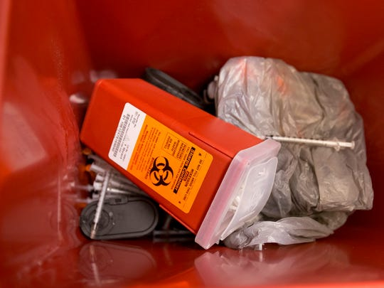 Needles and syringes that are awaiting proper disposal, some loose, and others bundled in a small sharps container in a larger sharps container at the Ithaca office of the Southern Tier Aids Program.