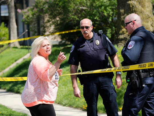 Police speak with a woman after a man was shot just