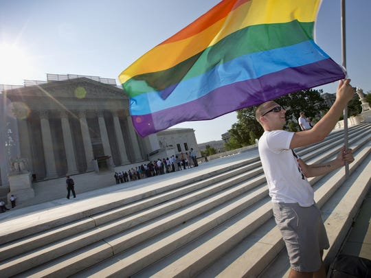 In this June 25, 2013, file photo, Vin Testa of Washington waves a rainbow flag in support of gay rights outside the Supreme Court in Washington.
