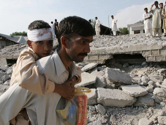 Oct. 8, 2005: 80,000 dead in Pakistan. Faiz Riaz who survived the deadly earthquake, is carried by his father to safer ground in Gari Habibullah, Pakistan, on Oct. 10, 2005.