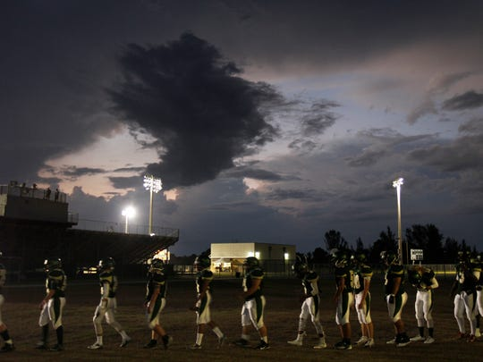 The Island Coast football team heads for the field after lengthy weather delay in 2015 in Cape Coral.