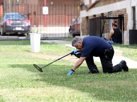 A crime scene investigator with Cincinnati Police searches the 900 block of Burton Avenue in Avondale on Tuesday morning near where Robin Pearl, 18, was shot and killed the night before. Police have arrested Joshua Maxton, 26, in the killing.