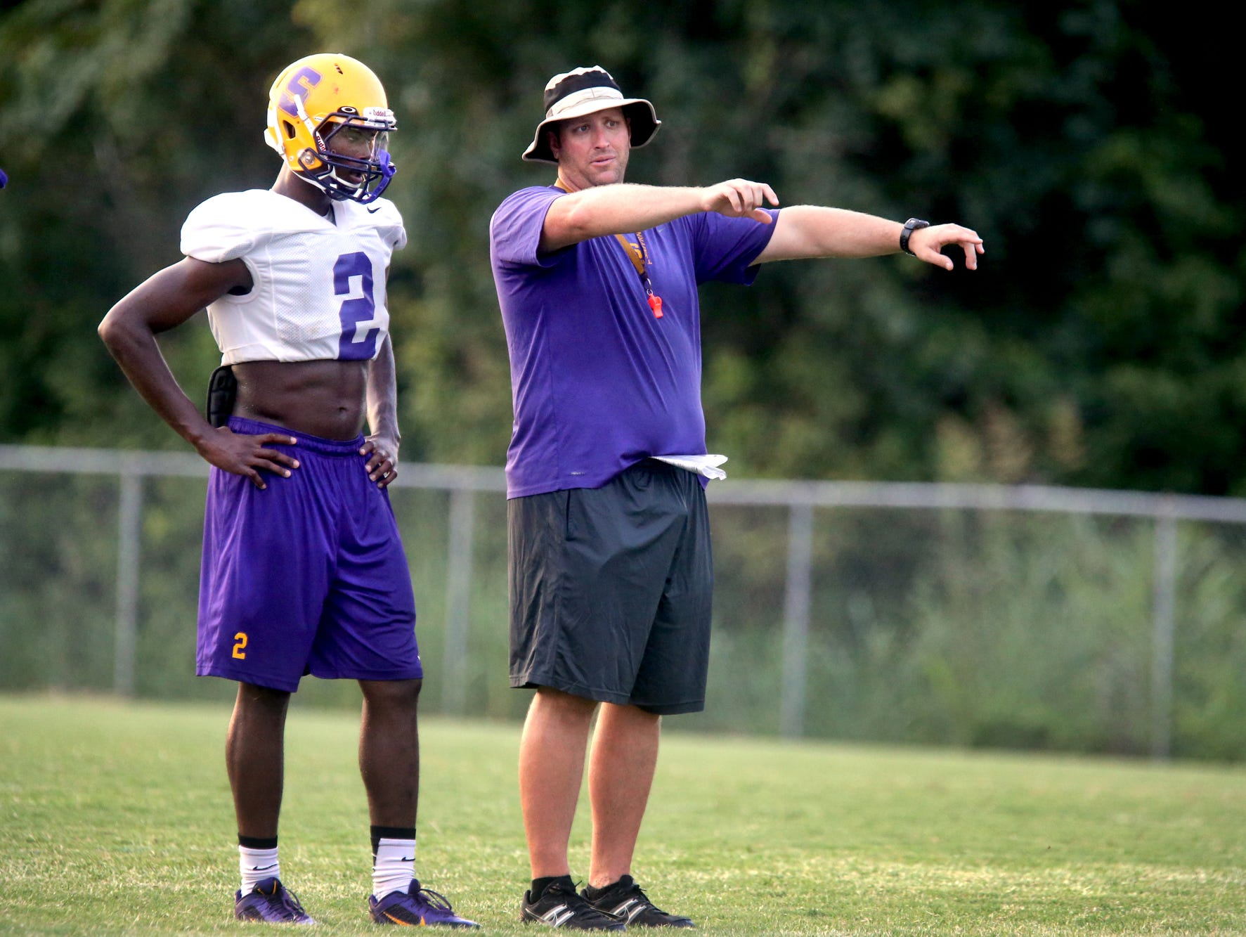 Smyrna Head Coach Matt Williams works with works with a player during the school's first day of pracitce with full pads on Monday, July 27, 2015.