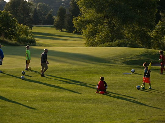 Players convene on the green area during a round of foot golf at Victor Hills Golf Club.