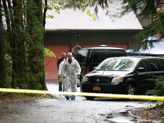 Law enforcement officials walk the crime scene after