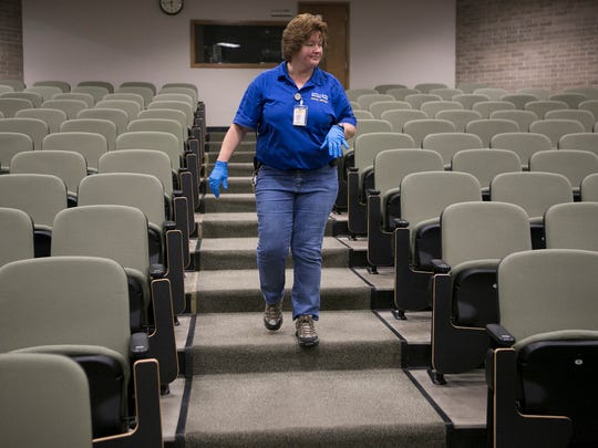 Custodian Patti Bembenek inspects a lecture hall for