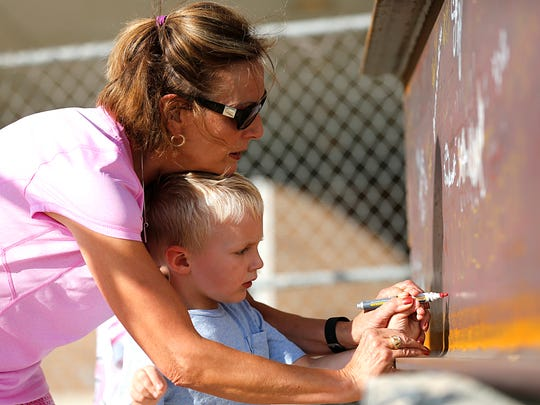 Dawn Colwin helps her grandson, Thaden, write his name on a steel beam which will be used in the contruction of the new addition to St. Marys Springs Academy. Dawn is a 1973 graduate, and Thaden is in 4k at the school. The beam has hundreds of signatures from past and present students and faculty. Monday September 28, 2015.
