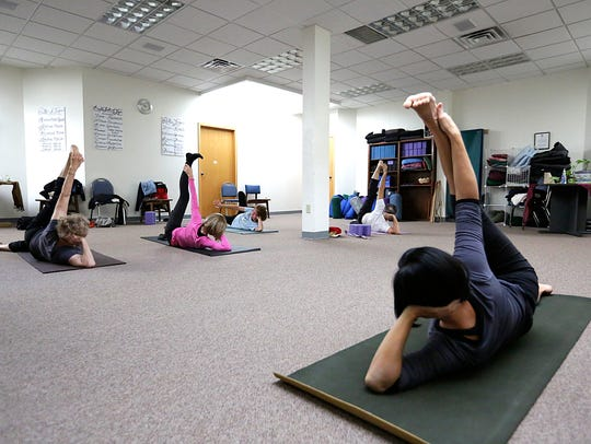 Lora Vahlsing (right) teaches her class yoga stretches