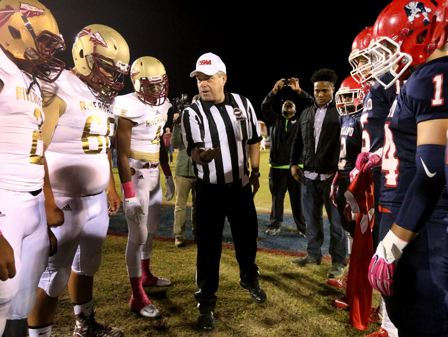 Head referee David Porter asks Riverdale to call a side before the coin toss at the begining of the Riverdale vs. Oakland game,also known as the Battle of the Boro. Oakland players carry the jersey of former teammate Jeremy McConville, who died in his sophomore year.