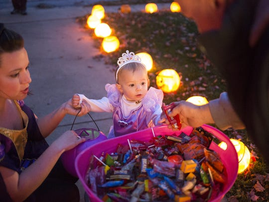 Aimee Friedrich and her daughter, Emma, 2, are given candy by Michael Rentzel. Family and friends remembered Connie and Anthony Zorbaugh, the couple who died in a September house fire, at a Halloween gathering in York.