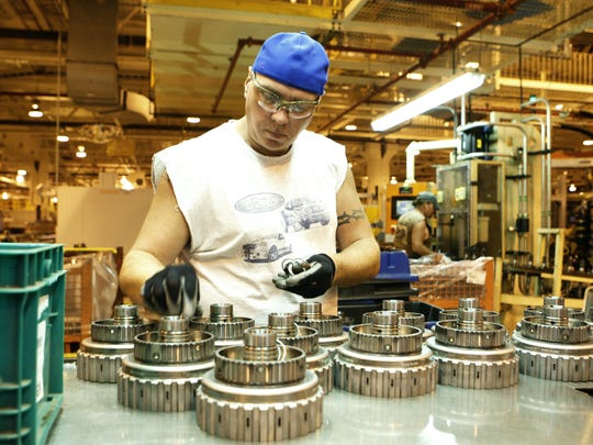 A worker builds a clutch for a transmission at the