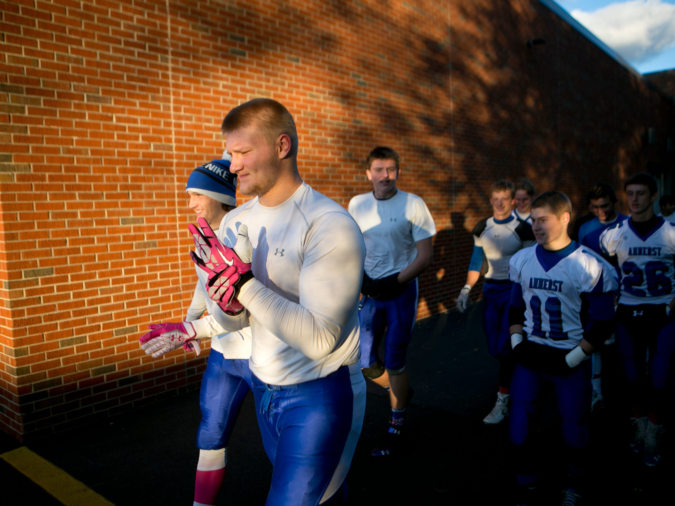 Seniors Garrett Groshek, left, and Tyler Biadasz, right, lead the team as they take to the practice field for warm-ups before playing Wittenberg-Birnamwood in the regular season finale, Friday, Oct. 16, 2015.