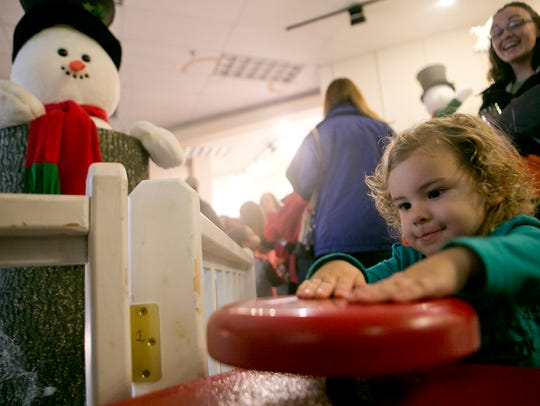 Kiana Haupt, 2, of Stratford pushes a button to move