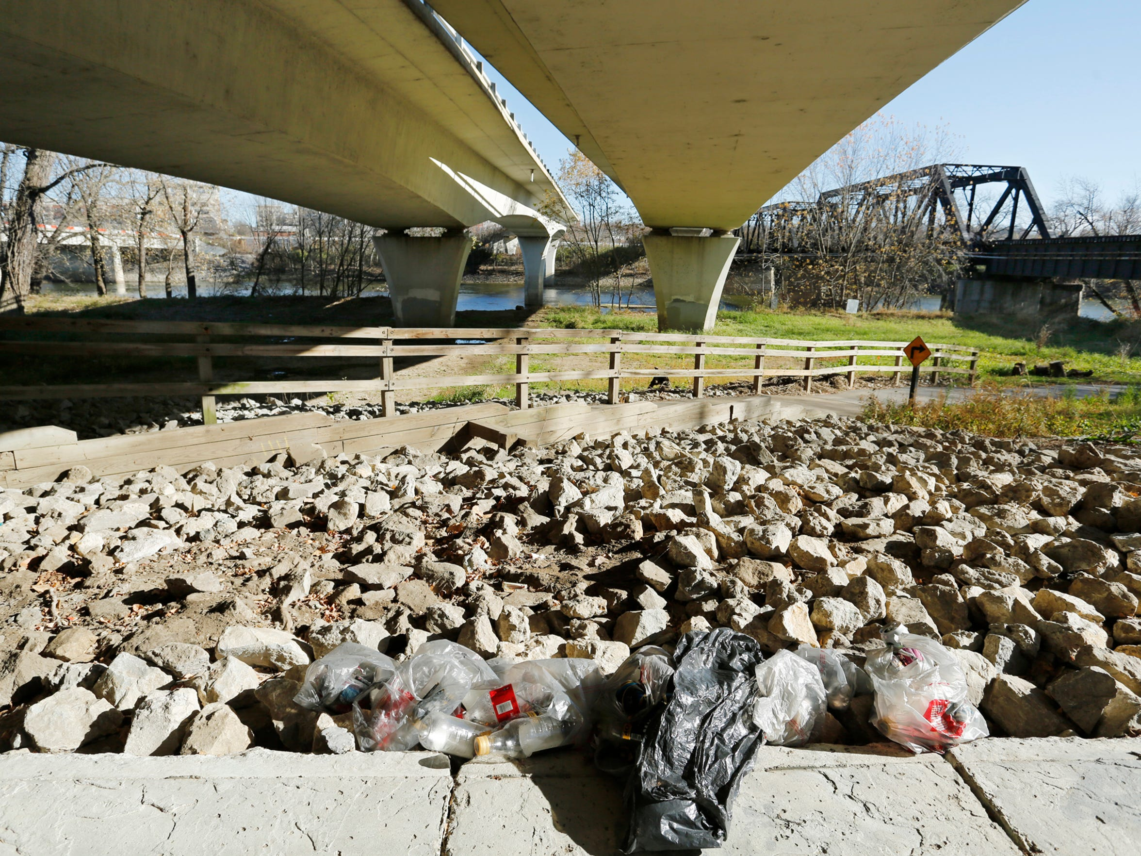 A pile of empty beer bottles and other trash left in plastic bags next to the Wabash Heritage Trail Thursday, November 19, 2015, beneath the State Street bridge in West Lafayette. A homeless man in the area said the trash was left behind by other homeless, who often gather beneath the bridge.