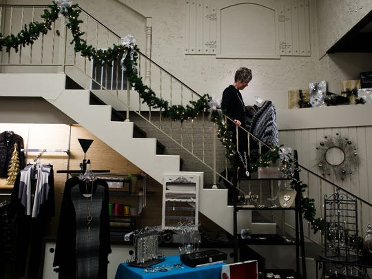 Style Works owner Sherri Windecker walks down the steps at her shop along Washington Ave  on Tuesday, November 24, 2015 in Iowa Falls. Windecker has been at her current location on Washington for 18 years and said that the project will be a total transformation for the downtown.