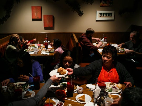 A family enjoys the this years Parks Community Thanksgiving dinner at Chucks Restaurant on Thursday, November 26, 2015 in Des Moines. 250 volunteers help to prepare, serve and deliver an estimated 4,000 meals.