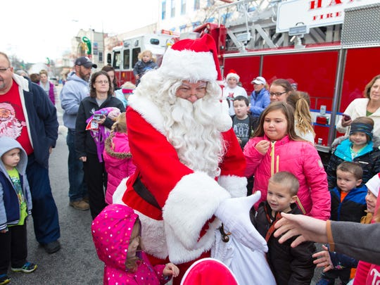 Santa Claus shakes hands after disembarking a Hanover Fire Department ladder truck during the Hanover Christmas Parade on November 27th, 2015.