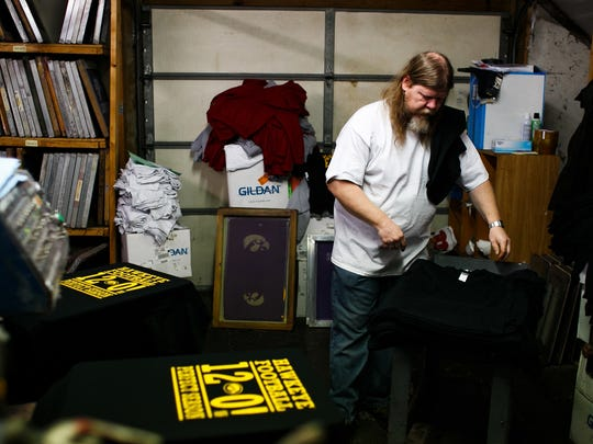 Chris Clifton, 44 from Ankeny prints t-Shirts commemorating the Iowa Hawkeyes 12-0 season at Strawberry Patch on Wednesday, December 02, 2015 in Ankeny.