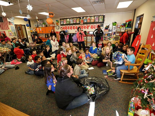Seventh graders watch from the back of the room while Ethan Hipolito-Picazo and other kindergartners unwrap gifts at Parkside Elementary school.
