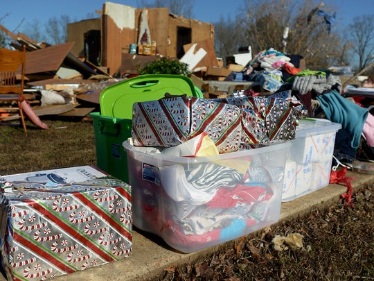 Christmas gifts are stacked outside a demolished home