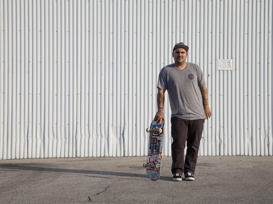 Subsect Skate Shop manager Kevin Jones, 34, stands with his skateboard in 2012.