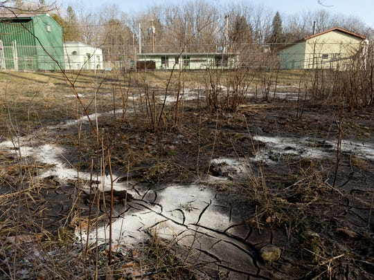 A soft, brown slurry of bacteria and sewage coats the ground on March 20, 2013 between the Trumansburg Wastewater Treatment Plant, background, and Trumansburg Creek after the first of four treatment stages at the plant overflowed.