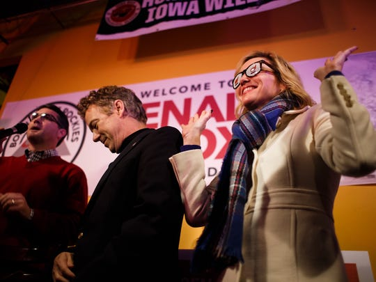 Kelley Paul, right, shows off a pair of Rand Liberty Glasses she received as a present during a birthday party for her husband and republican presidential candidate Rand Paul, left, who celebrated his 53rd birthday at Buzzard Billy's on Thursday, Jan. 07, 2016, in Des Moines.